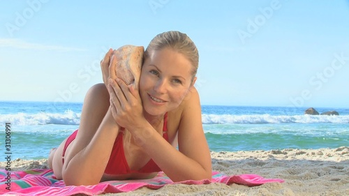 Attractive blonde woman listening to a shell