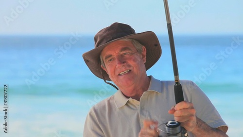 Mature man fishing from the beach