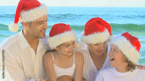 Happy family wearing Christmas hats and singing on a beach