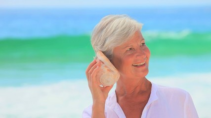 Elderly white-haired woman listening to a shell