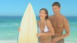 Sweet couple laughing while holding a surfboard