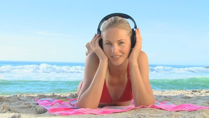 Woman lying on a beach listening to music