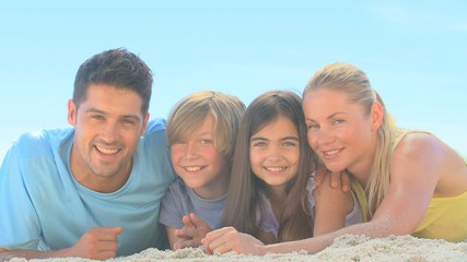 Cute family lying on a beach