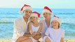 Happy family wearing Christmas hats on a beach