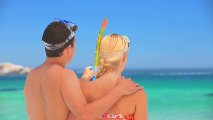 Cute couple wearing snorkels and masks
