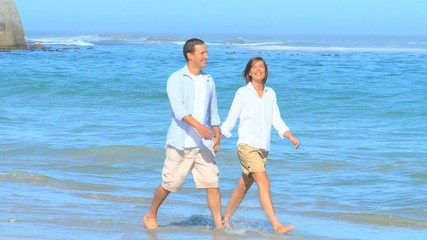 Happy couple walking on a beach