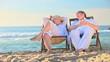 Elderly couple sitting in deckchairs on a beach