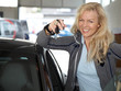 Attractive female holding keys of new car