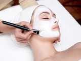 cosmetician applying facial mask on female face poster