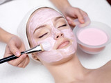 Girl receiving cosmetic pink facial mask - 31311707