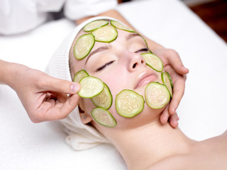 Woman receiving facial mask of cucumber