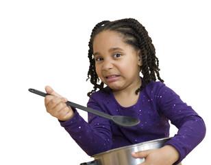 Enfant faisant la grimace en goûtant la soupe