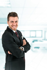 Smiling young businessman in his office