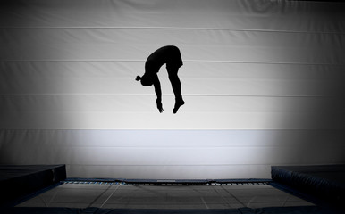 silhouette of jumping man on trampoline doing somersault