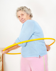 portrait senior lady doing gymnastic with hula-hoop