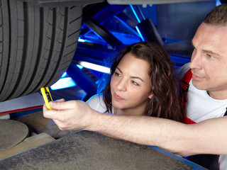 Motormechanic and customer checking the tread depth of a tyre