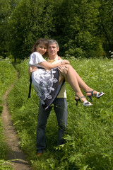 Man carry woman on hands on summer meadow