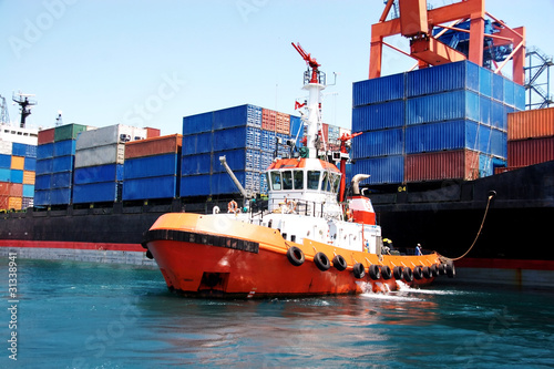 canvas print picture Tug boat pulling out container ship