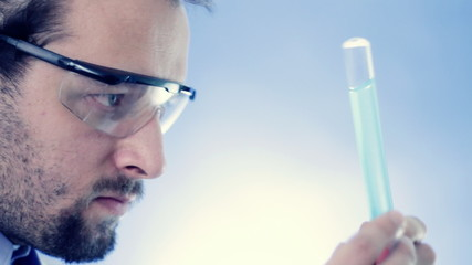 Male scientist examining test tube with blue liquid