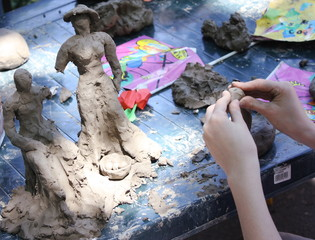 Child building clay statues