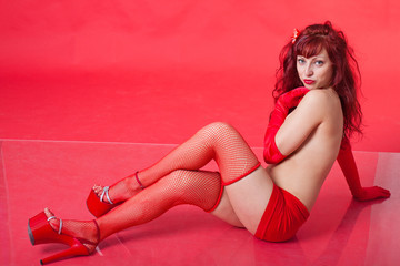 portrait of sexy young red-haired woman on red background