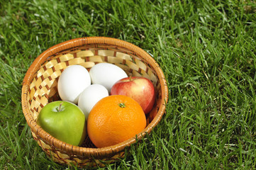 Wicker basket with fruits and eggs on grass