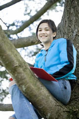 Preteen girl sitting in tree writing in journal or notebook