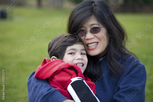Beautiful asian mother holding her disabled son at park