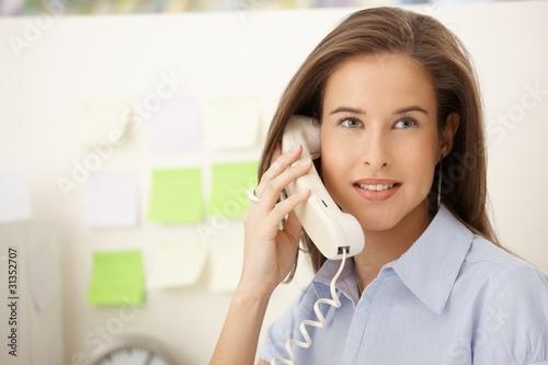 Portrait of woman on landline call - 31352707