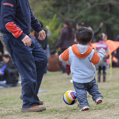 baby playing football with his father