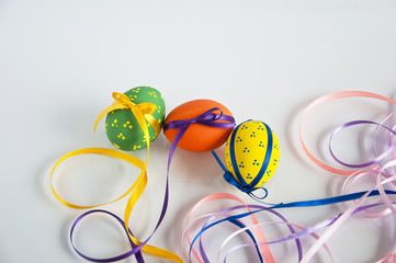 Three painted eggs wrapped with ribbon bows