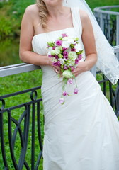 A bride in a white gown holding a boquet of flowers