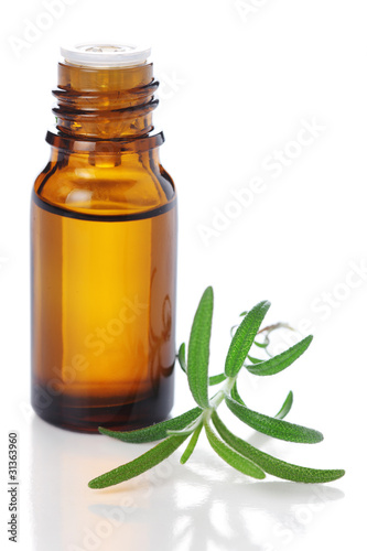 bottle of aromatic essence oil and fresh rosemary on white isola