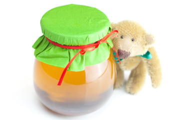 teddy bear  and  jar of honey  isolated on white