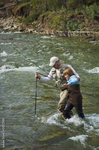 Father And Son Crossing A Mountain Fly Fishing River