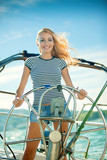 The beautiful girl operates the yacht