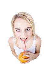 Frau trinkt mit Strohhalm direkt aus Orange, witzig