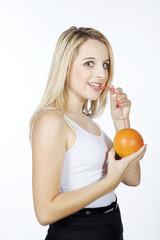 Frau trinkt mit Strohhalm direkt aus Orange, seitlich