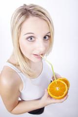 Frau trinkt mit Strohhalm direkt aus offener Orange, seitlich