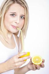 Frau trinkt mit Strohhalm direkt aus Zitrone, saurer Blick