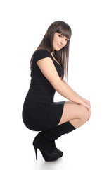 Cute brunette in black dress and boots, isolated on white