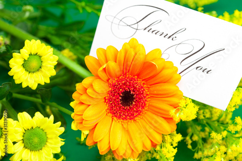 yellow daisy,gerbera and card signed thank you on green backgrou