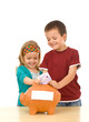 Grinning kids stuffing piggy bank