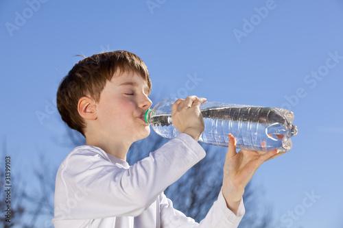 neunjähriger Bub trinkt aus Wasserflasche - 31399103