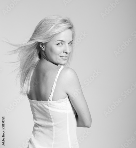 Portrait of beautiful blonde woman in slip embracing