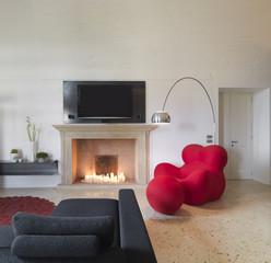 lussuoso soggiorno con poltrona rossa vicino al camino