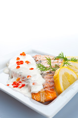 Steak from a salmon with creamy sauce and caviar..