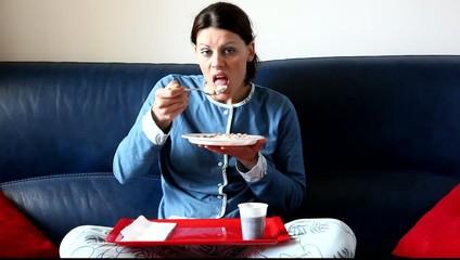 Bella ragazza che mangia sul divano davanti alla tele