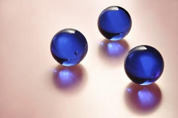 Синие стеклянные шары с отражением на розовом фоне