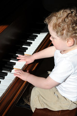 Young boy plays piano in sunlight